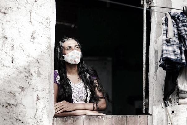 마스크를 쓰고 창문 밖을 보고있는 여성